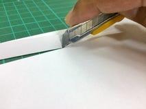 Coupez le papier avec un couteau Photos libres de droits