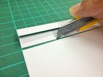 Coupez le papier avec un couteau Photographie stock libre de droits