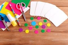 Coupez les cartes et entourez, des ciseaux, crayon, le bâton de colle, feuilles colorées de carton sur une table en bois Comment  Image stock
