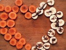 Coupez les cercles de carotte et de banane formant le coeur Image stock