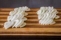 Coupez les demi anneaux d'oignon sur une planche à découper pour la cuisson Photo stock