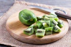 Coupez les morceaux de kiwi vert sur la planche à découper en bois Photo libre de droits