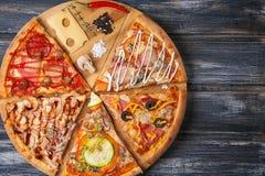 Coupez les morceaux de pizza avec différentes saveurs, sans une seule pièce, sur une table en bois Images libres de droits