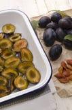 Coupez les prunes dans une cuvette d'émail Photo stock