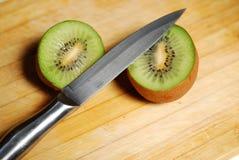 Coupez par un kiwi sur le hachoir Images stock