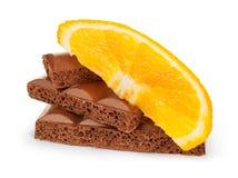 Coupez rudement les gros morceaux d'une barre de chocolat avec le fruit orange Photo libre de droits