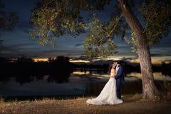 Coupld del recién casado por el lago en la puesta del sol Fotos de archivo libres de regalías