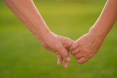 Couple& x27; руки s на зеленой предпосылке Стоковое Фото