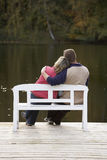 Couple-1. Couple sitting on a bench at a lake in autumn stock images