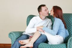 Couple 13. Young couple enjoying a kiss on a couch royalty free stock photos