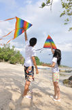 COUPLE. Flying kites in small fishing village seaside royalty free stock image