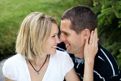 Couple 2. Young attractive Caucasian couple sitting together in nature with heads together and smiling Stock Image