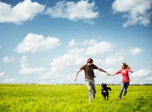 Couple. Young happy couple running on a green meadow with a dog Stock Photos