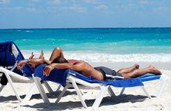 Couple. Beautiful Carribbean beach with white sand umbrella and blue seating, couple tanning Stock Images