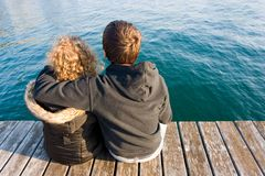 Couple. Photo of a young couple sitting on a dock Royalty Free Stock Photo