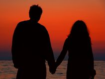 Couple. Holding hands at sunset royalty free stock photo