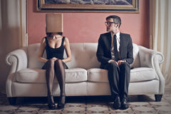 Couple. Young men looks beautiful women with head in the box Royalty Free Stock Photography