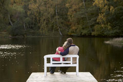 Couple-3. Couple sitting on a bench at a lake in autumn royalty free stock photos