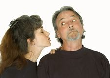 Couple. An attractive middle aged man and woman interact as the woman prepares to kiss the man on the cheek