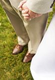 Couple. Bride and groom holds hands on grass Royalty Free Stock Photo
