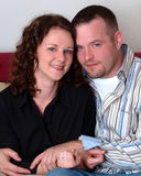 Couple. Smiling young married couple sitting together in their home Royalty Free Stock Photos