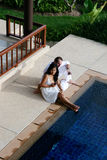 Couple. Attractive multicultural couple by the swimming pool Stock Images