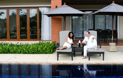 Couple. Attractive multicultural couple by the swimming pool Stock Image