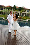 Couple. Attractive multi-cultural couple dancing by the swimming pool Royalty Free Stock Photography