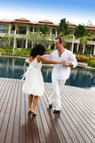 Couple. Attractive multi-cultural couple dancing by the swimming pool Stock Images