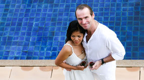 Couple. Attractive multicultural couple enjoying red wine by the swimming pool Royalty Free Stock Photography