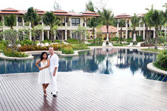 Couple. Attractive multi-cultural couple by the swimming pool Stock Image