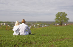 Couple. Sitting on a green meadow Royalty Free Stock Image