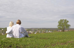 Couple. Sitting on a green meadow Stock Images