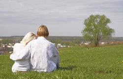 Couple. Sitting on a green meadow Stock Image