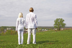 Couple. Standing on a green meadow stock image
