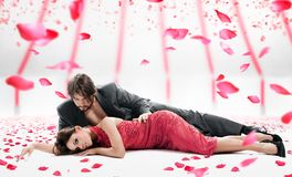 Couple. Attractive couple over falling rose petals Stock Photo