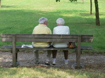 Couple. Older couple sitting on a park bench royalty free stock photo