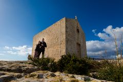Couple above high Dingli cliffs. Young couple above high Dingli cliffs on Malta island. Beautiful landscape with people and church in south Europe royalty free stock photography