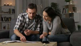Couple accounting checking receipts at home. Serious couple accounting checking receipts using a calculator sitting on a couch at home stock footage