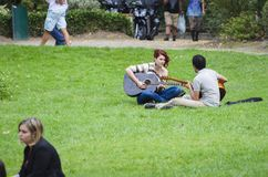 A couple with acoustic guitars. TOULOUSE, FRANCE - OCTOBER 4, 2014: A couple with acoustic guitars enjoy the day in a city park Stock Images