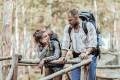 Couple of active backpackers standing somewhere in forest and talking. Somewhere in forest. Couple of active backpackers feeling relaxed and rested while royalty free stock photos