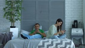 Couple addicted to smartphones phubbing at home stock video