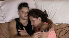 Couple addicted to social media networks spending time in bed together texting everyone on their smartphones stock video