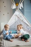 Couple male toddlers enjoying movement and simple games in cosy sunny nursery. Couple adorable toddlers enjoying movement and simple games playing in cosynursery stock photography