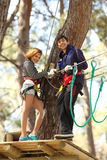 Couple in adventure park. Happy young couple climbing roped up in adventure park, smiling to the camera Stock Images