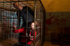 Couple afraid Halloween victims imprisoned in a metal cage looki Royalty Free Stock Photography