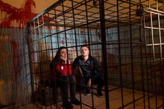 Couple of afraid Halloween victims imprisoned in a metal cage wi Stock Photography