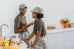 Couple of african american army soldiers talking in kitchen stock images