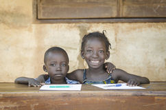 Couple of African children sitting in their desk working on home. Smiling Black Children: African Ethnicity Education Symbol Schooling Royalty Free Stock Image