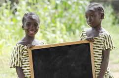 Couple of African children standing outdoors with a big blackboard. Girls standing and holding signboard and looking at camera in front of building Royalty Free Stock Photography
